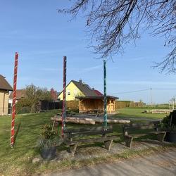 """Dorfplatz """"Generationen-Treffpunkt"""" mit drei Stelen von Gudrun Hübsch. Das  silberne Band um die Stelen symbolisiert die Lohmarer Flüsse und Bäche, in der mittleren Stange zusätzlich von Kindern mit Coronasteinen besetzt"""