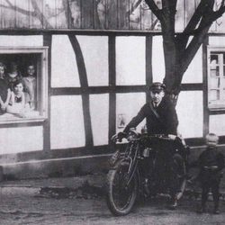 Dr. med Pütz mit Kind Rolf Heimann 1925 im Aggerhof. Dort hielt damals der Omnibus der Kraftverkehrslinie Wupper-Sieg.