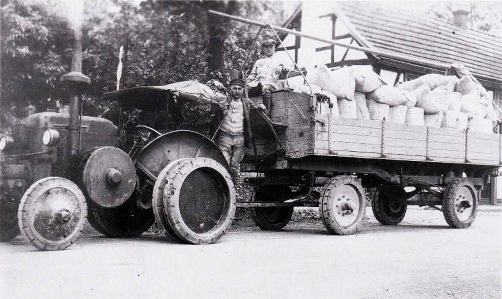 """Fritz Bräunsbach, Aggerhof auf """"Lanzbulldog"""" 1928 in der Mühle Frackenpohl in Kreuznaaf. Auf dem Anhänger sitzt Herr Kallet."""