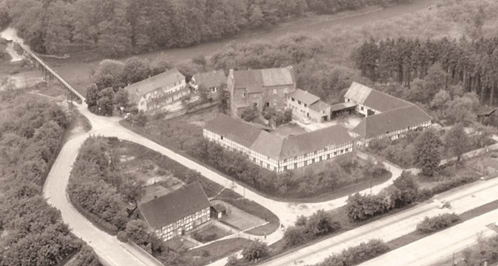 """Burghaus mit Vorburg und Bachhof (links), Gasthaus """"Zur alten Fähre"""" und der Notbrücke über die Agger Ende 1950er Jahre"""