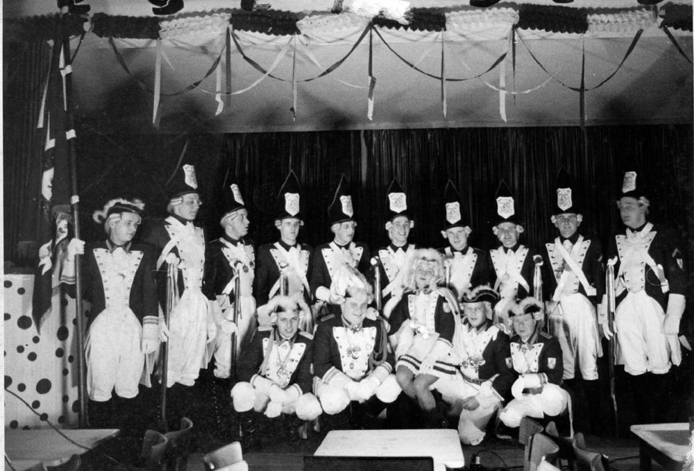 """KAZI Funken""""Rut Wieß""""1964 im Festzelt (der Saal im """"Hotel zur Linde"""" war im Winter 1958/59 abgebrannt). Vlnr hinten: Walter Boer, Walter Oleschkowitz, Peter Ramme, unbekannt, Rudi Furk, Heribert Frielingsdorf, Dieter Limbach (Fuzzi), Manfred Frost (Coon), Herbert Nöttel und Paul Ramme; vorne: Bernhard Labitzke, Werner Knorre, Marlies Pullem, Horst Pütz und Georg Stöcker."""