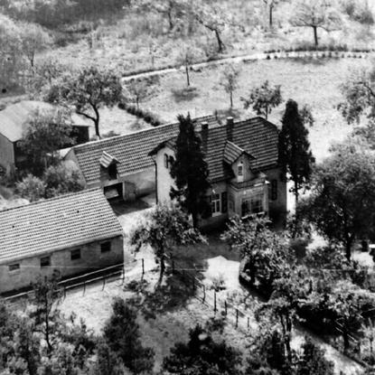 Haus Waldeck Mitte 1950er Jahre. Bildmitte Wohnhaus, dahinter ein Anbau mit Waschküche, Garage und Ställe für eine Kuh und ein Schwein, dahinter eine Scheune; links im Bild der Pferdestall