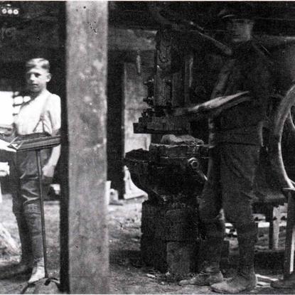 """Anfang der 1930er Jahre im """"Panneschopp"""". Bei dem Gerät rechts handelt es sich um eine Revolverpresse zum Pressen von Abdeckpfannen. links: Otto Fischer (""""Pannemann"""" sen.), der an einem Pult steht. Hier wurden die letzten Feinarbeiten an der Dachpfanne vollendet. rechts daneben: Karl Schröder; links an der Maschine: J. Lapp"""