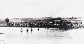 """Wettschwimmen im """"Strandbad Wahlscheid"""" in den 1930er Jahren. Am Aggerufer haben sich zahlreiche Zuschauer eingefunden. darunter Parteigrößen und Ortspolizist Grammich."""