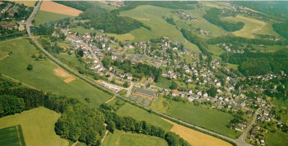 Bild (1990/91) Mitte: Kath. Kirche St. Bartholomäus gegenüber Forum neben dem früheren Bahnhof. Hintergrund rechts: Emmersbach, Katharinenbach, Schönenberg, Höffen
