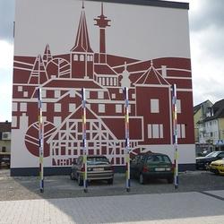 Stelen von Peter Flier, Frouardplatz (Die Hausfassade wurde im Auftag der Familie Heinen mit Fördergeldern der Stadt gestaltet von dem Stuckateurmeister und Restaurator Thomas Söntgerath aus Krahwinkel)