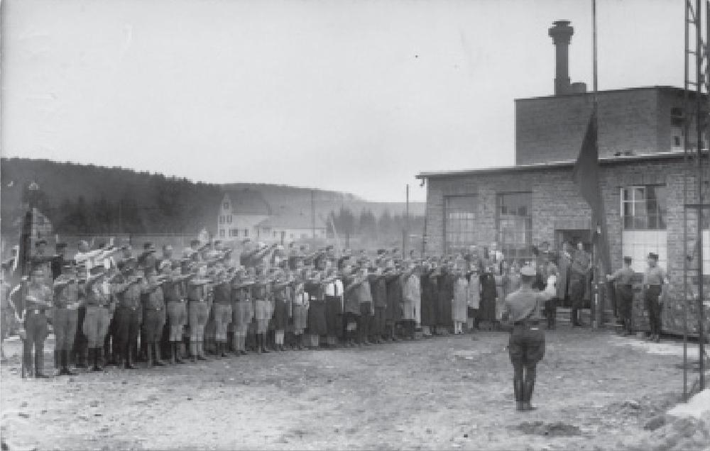Bannerhissen 1936 auf dem Fabrikgelände der Firma Fischer in der Hermann-Löns-Straße. Links neben der Tür der Fabrikant Johann Fischer(mit Hut) und rechts daneben seine Ehefrau Mechtilde. Das helle Haus im Hintergrund ist das Haus Höndgesberg auf der Kieselhöhe.