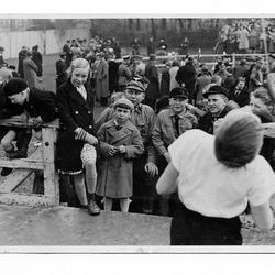 """""""Würstchenfangen""""auf der Tribüne, auf der vorher die Maikundgebung stattfand. Vorne das blonde Mädchen in dem dunklen Mantel ist Christel Broicher, verh. Schulten und der Junge rechts daneben ist Rainer Fischer."""