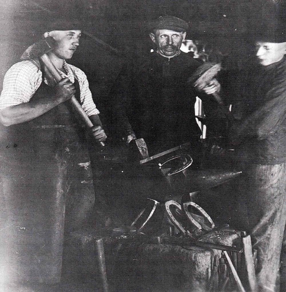 """3 Männer Maylahn in der Schmiede Kaltwinkel  Sie beschlagen ein Hufeisen auf dem """"Ampes"""" (Amboß), dem Mittelpunkt der Schmiede, Ende der 30er Jahre. In der Mitte Vater Karl M. mit den Söhnen Max (links) und Otto (rechts)."""