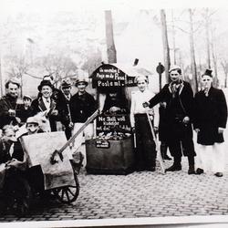 """Fastnachtsumzug 1938. Damals kam das Fastnachtslied auf """"ne Stall voll Küchelche met decke Büchelche un nevebei e Pösje an de Poss"""", das Peter Büscher mit einem fahrbaren Postschalter umsetzte."""